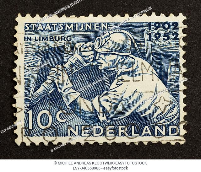 HOLLAND - CIRCA 1950: Stamp printed in the Netherlands shows a miner in action, circa 1950