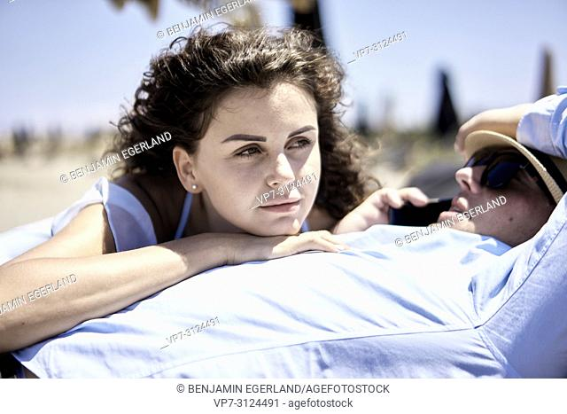 woman relaxing on belly of busy business man using phone for call, holiday, summer, vacations, couple, work-life balance