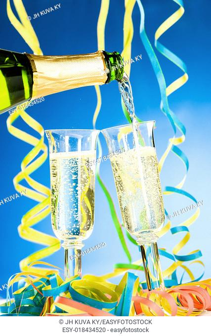 A bottle and two glass of sparkling wine, streamers and blue background
