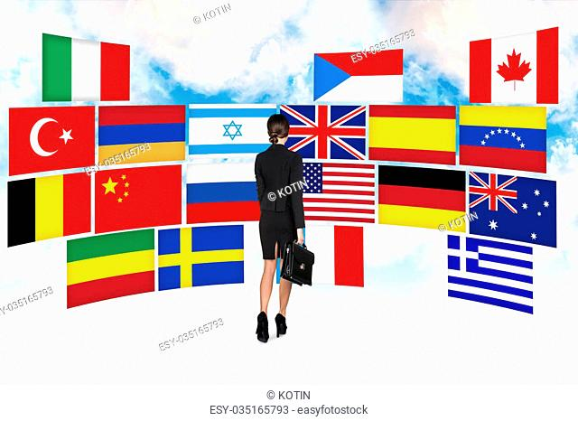 Business woman stands on the many different countries flags background