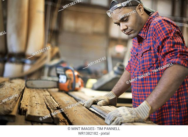 A reclaimed lumber workshop. A man measuring and checking planks of wood for re-use and recycling