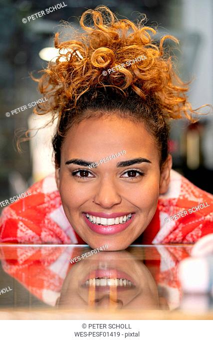 Young woman working in fashion store, leaning on counter