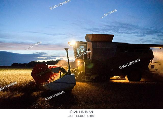 Combine Harvester Harvesting Wheat Crop At Night