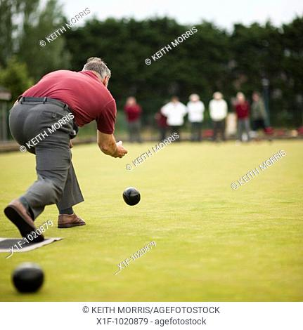 A man playing lawn green bowls, UK