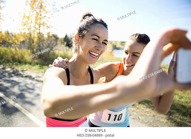 Laughing runners taking selfie on sunny path