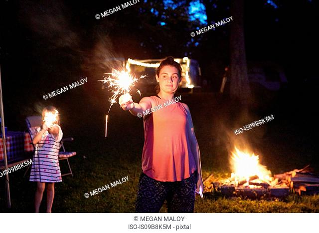 Two girls standing near camp fire, using sparklers