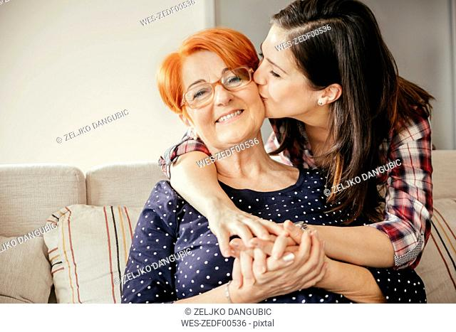 Happy adult daughter embracing and kissing mother