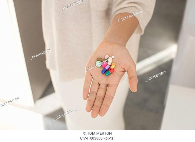 Woman holding, showing multicolor pills