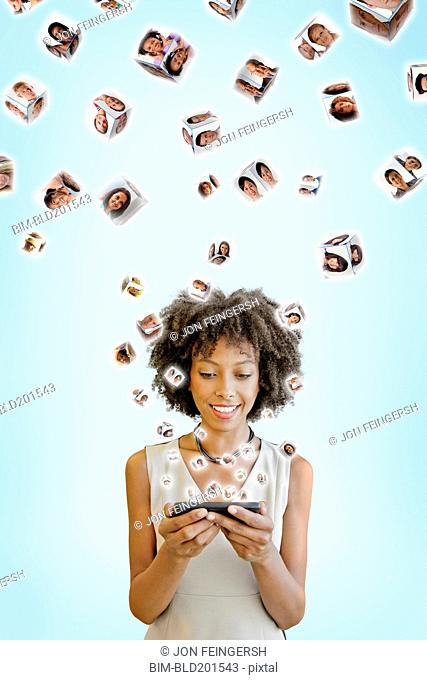 African American woman using cell phone with images floating above
