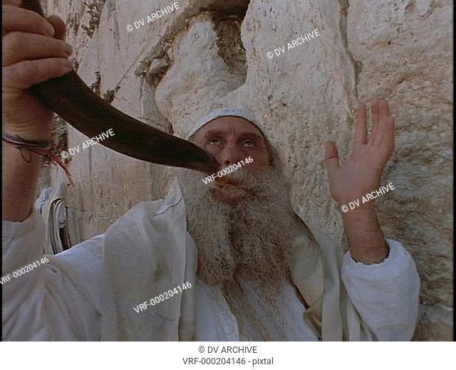A man blows a shofar at the Western Wailing Wall