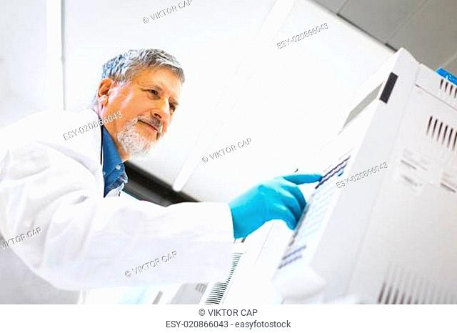 Senior male researcher carrying out scientific research in a lab using a gas chromatograph (shallow DOF color toned image)