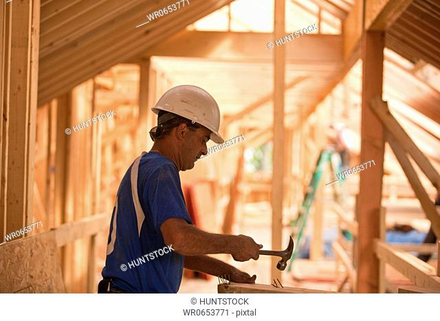 Hispanic carpenter hammering nails on board at a house under construction