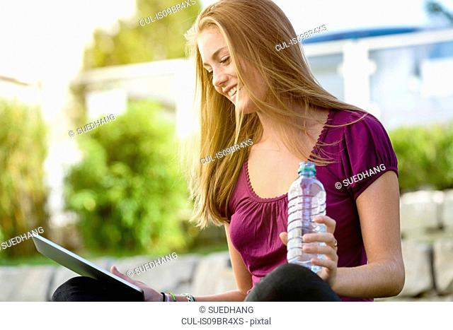 Young woman using digital tablet in park