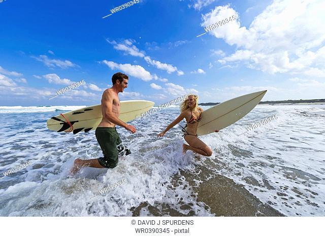Two surfers run through the waves having fun