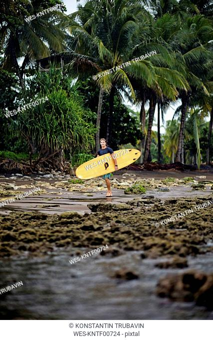 Indonesia, Java, man carrying surfboard at the coast