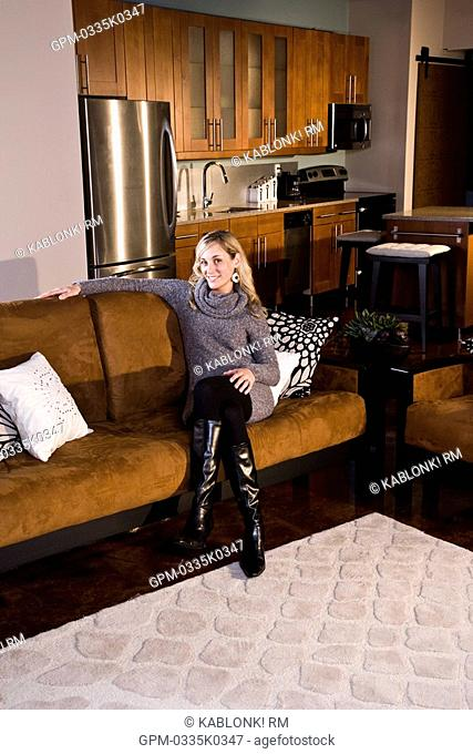 Young woman sitting on couch in modern apartment