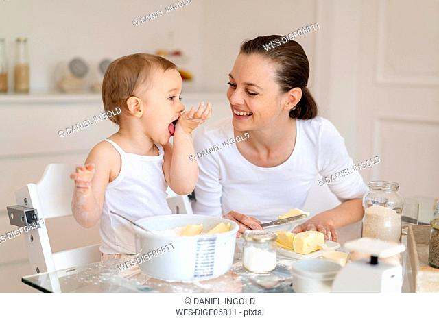 Happy mother and little daughter making a cake together in kitchen at home