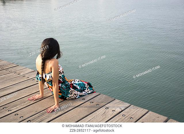 Rear view of a young woman sat on the wharf by the sea