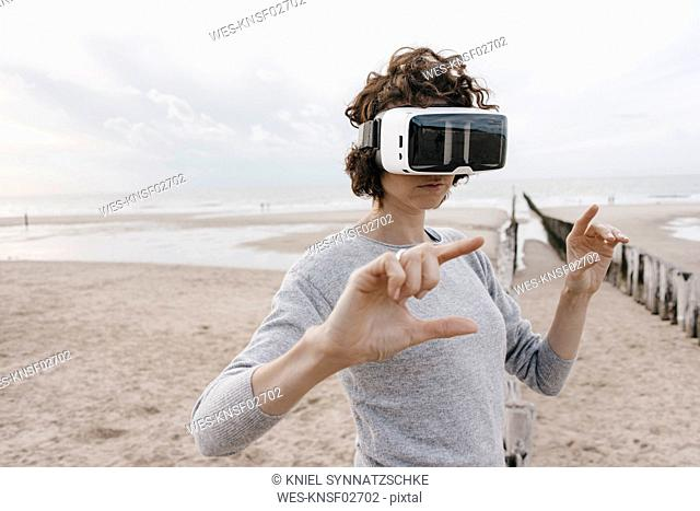 Woman on the beach wearing VR glasses