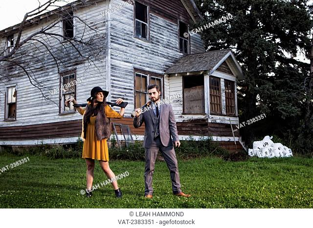 A man and woman dressed in vintage clothing holding weapons in front of a house and bag of money; Edmonton, Alberta, Canada