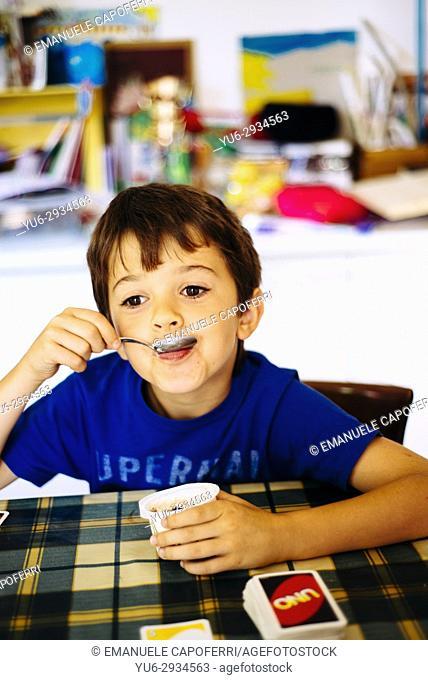 child eating yogurt in the kitchen