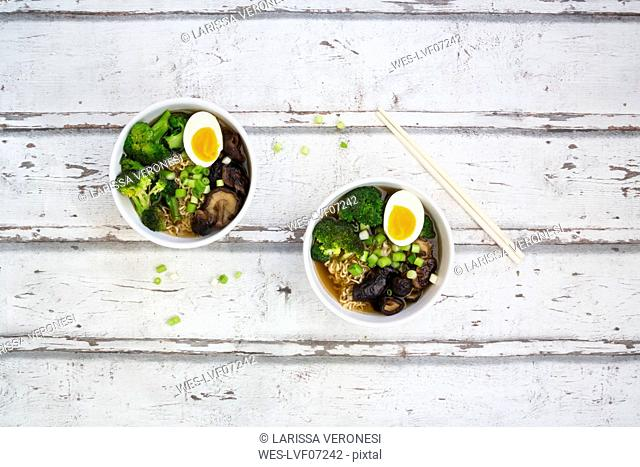Two bowls of Ramen soup with egg, broccoli, noodles, shitake mushroom and spring onions