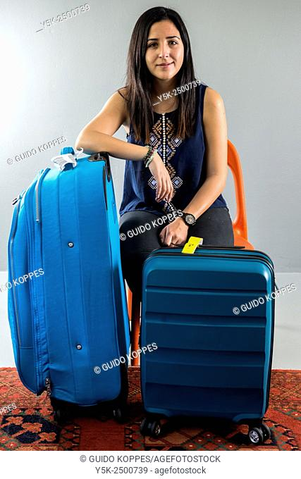 Tilburg, Netherlands. Young, South-American brunette female with suitcases used for travelling. Studio-shot