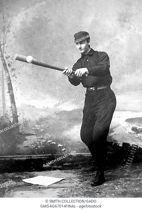 An unidentified baseball player is shown wearing a dark uniform, he is hitting a baseball that was thrown to him by a person who is out of frame