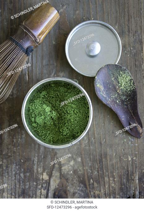 Matcha in a tea caddy, a matcha spoon and a tea whisk