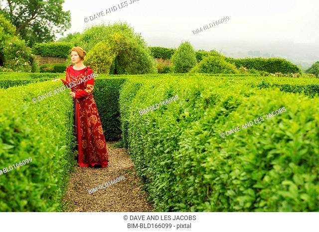 Woman in medieval costume standing in hedge maze