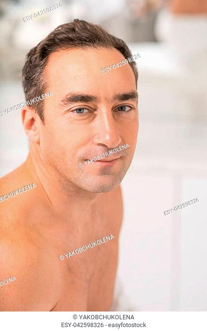 Happy middle-aged man is sitting and relaxing at spa. He is looking at camera and smiling