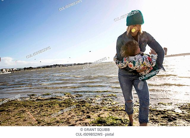 Mother and toddler girl on beach