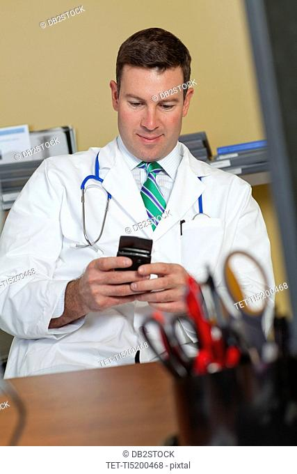 Male doctor text messaging