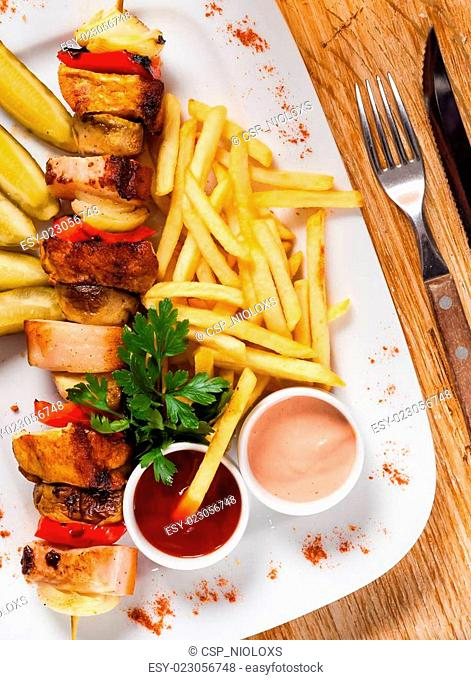 Chips and skewers on a white plate
