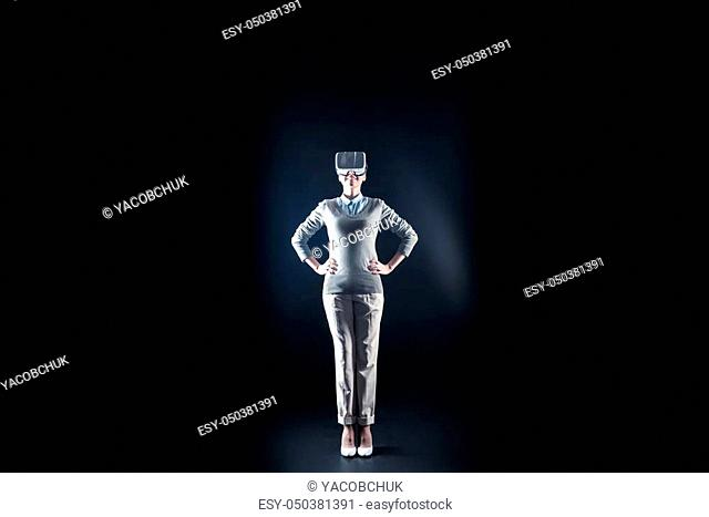 3d dimension. Positive cheerful nice woman standing against black background and looking up while being in 3d dimension