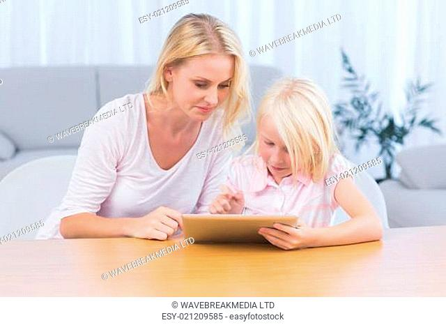Little girl using laptop while her mother is reading on the couch in the living room