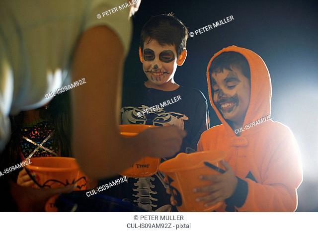 Three children wearing halloween costumes trick or treating