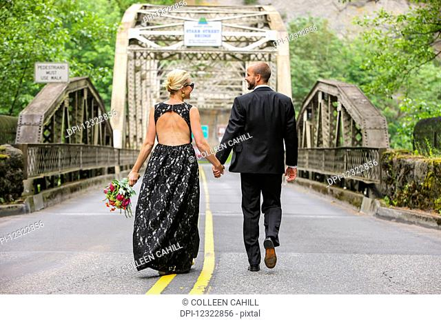 A bride and groom holding hands and walking down a paved road; Oregon, United States of America