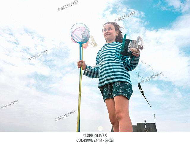 Girl holding fishing nets looking away smiling
