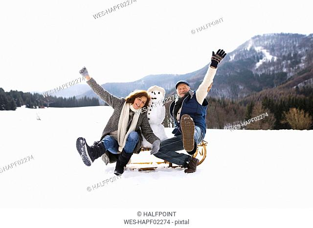 Senior couple posing with snowman on sledge in winter landscape