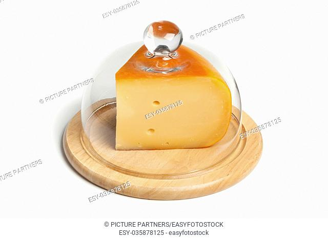 Piece of Dutch Gouda cheese on a wooden board covered with a glass hood