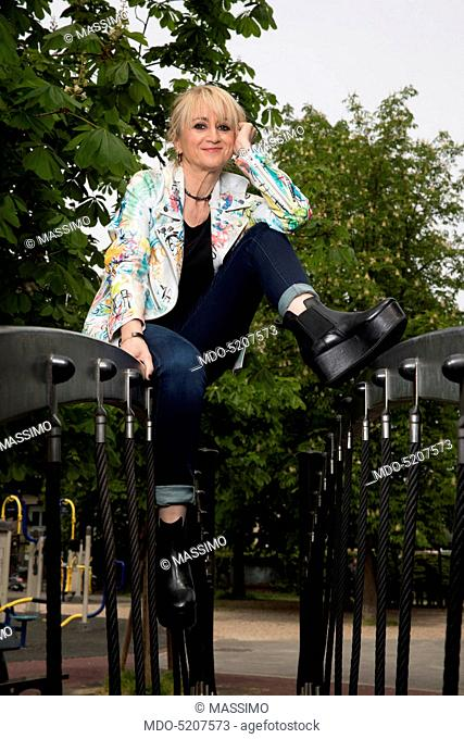 Actress and comedian Luciana Littizzetto sitting in a playground inside the public park Parco del Valentino. Turin, Italy. 21st April 2016