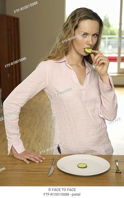 A blonde woman having a slice of cucumber