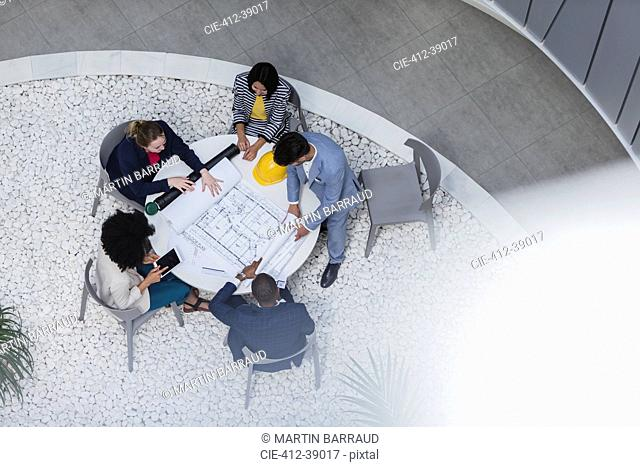 Architects reviewing blueprints, planning at table