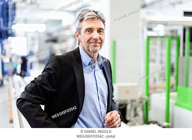 Smiling businessman in production hall