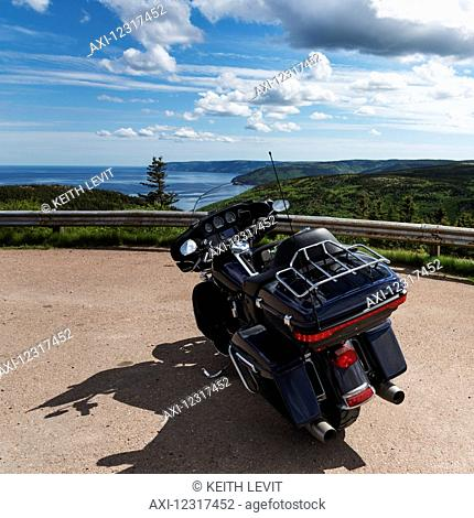 A motorcycle parked at a roadside lookout with a view of the coastline and ocean, Cape Breton Highlands National Park; Pleasant Bay, Nova Scotia, Canada