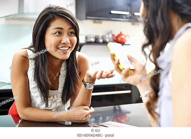 Two young women in kitchen with mobile phone