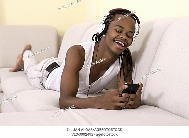 Cheerful black man in headphones lying on sofa and using smartphone