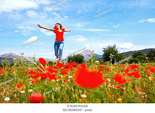 Woman running in poppy field, Palma de Mallorca, Islas Baleares, Spain, Europe