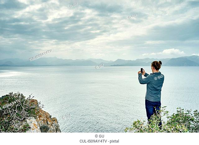 Young man standing on cliff photographing with smartphone, Alcudia, Majorca, Spain
